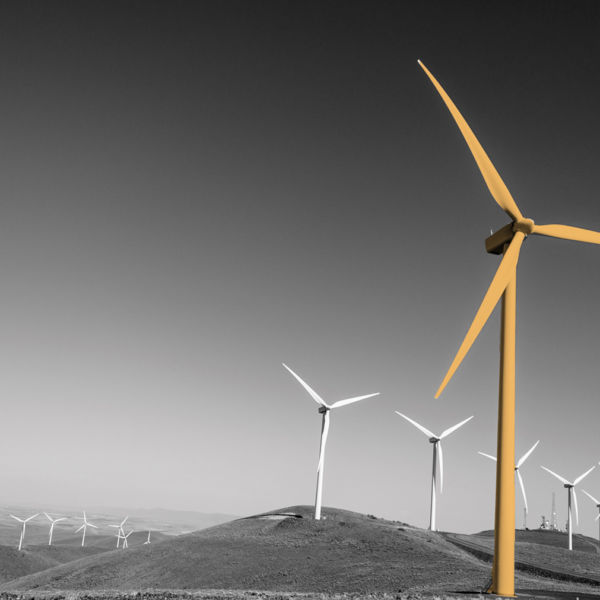 Power turbine wind mills on rolling hills with a blue sky